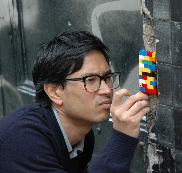une personne répare un mur avec un lego